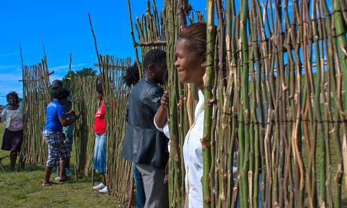 Kenneth Magaga with his team from Qolweni hold up their sections of Running Fences at the Human Fence gathering towards the end of Erica Lüttich's two week residency for Site_Specific.