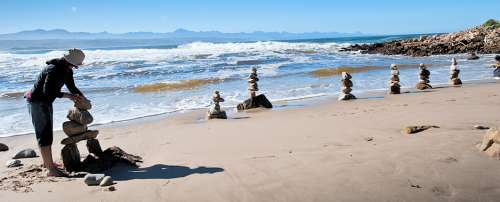 Hannelie Coetzee is one of the 2011 artists that have been invited back in 2013 to provide a sense of continuity and experience between both land art events. Here she is in the process of installing 'Familie Portret' (Family Portret) at Lookout Beach in Plettenberg Bay using selected stones with bands of quartz. Photo: Elizabeth Olivier-Kahlau.